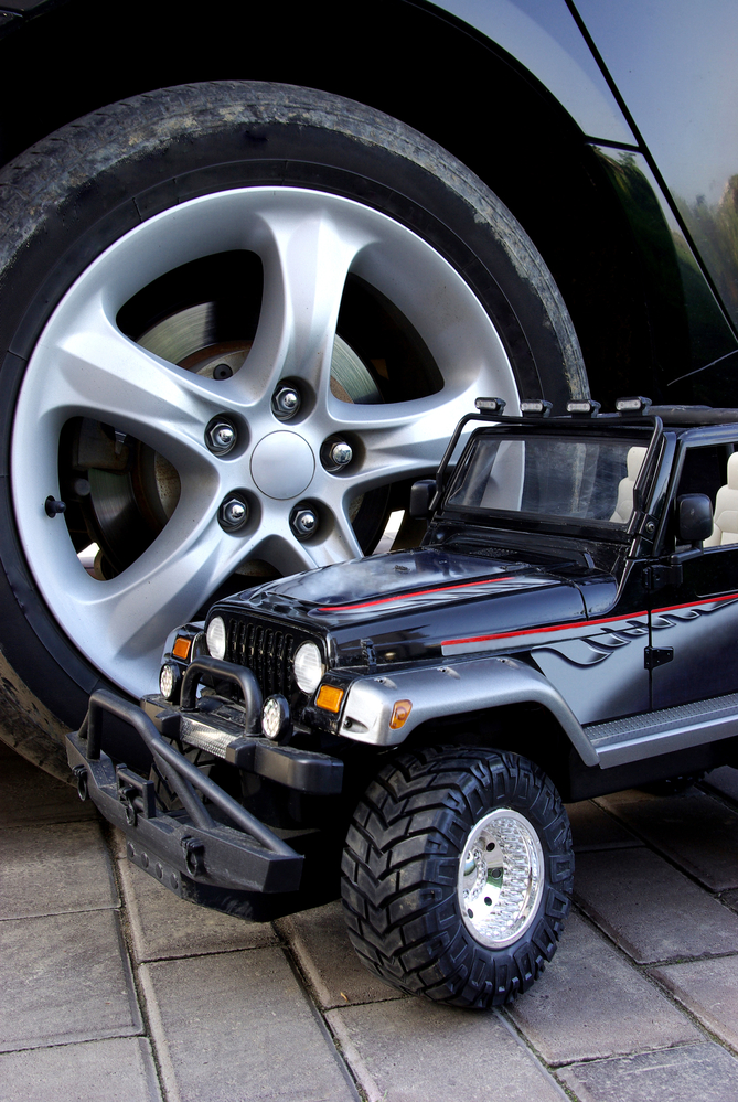 a jeep toy for kids in front of a read jeep tire on a driveway