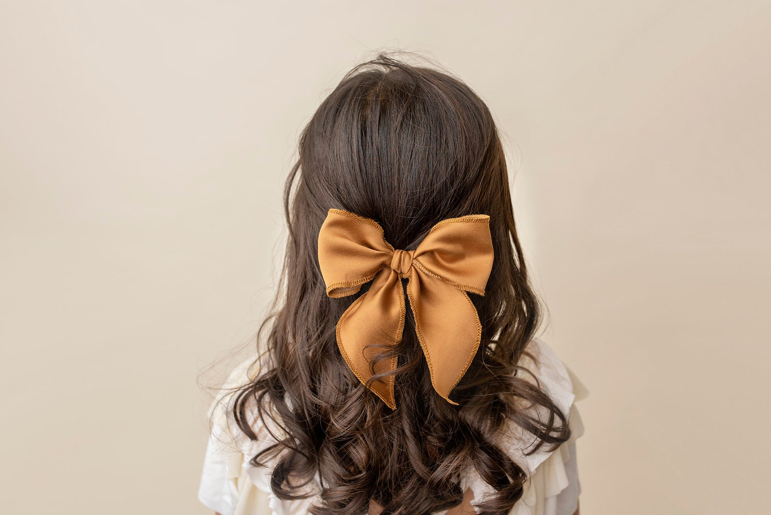 a mustard yellow sailor boutique bow in a girls wavy brown hair