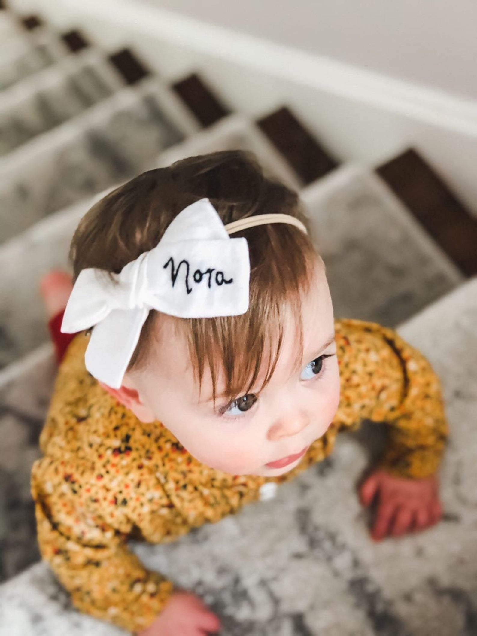 a baby wearing a white boutique hair bow headband with her name embroidered on it