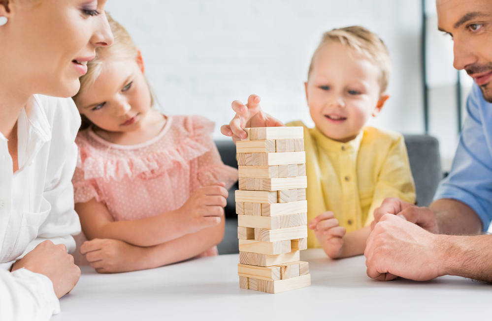 A family of 4 playing Jenga as a fun evening activity for kids