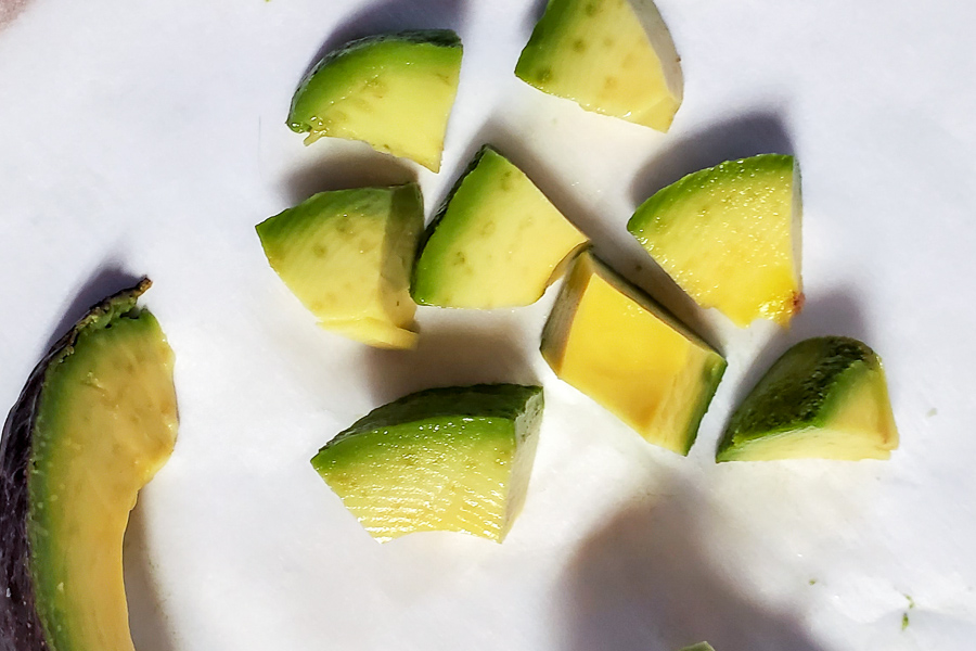 chopped up avocado for babies on a white background
