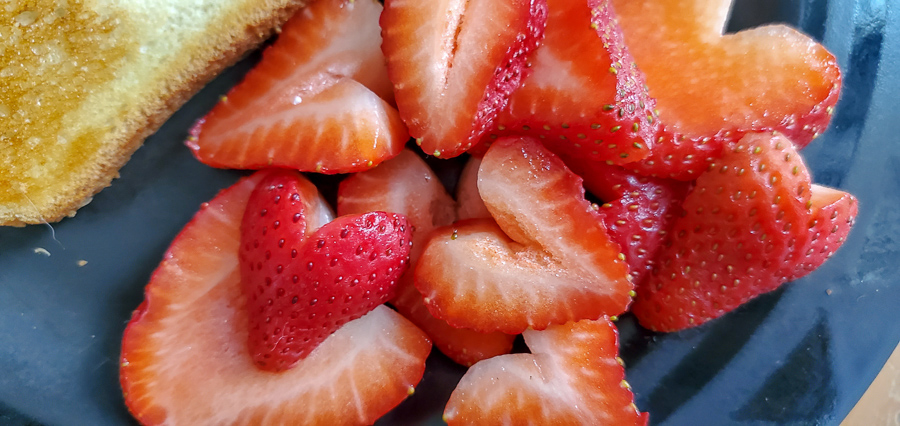 a breakfast plate with strawberry hearts