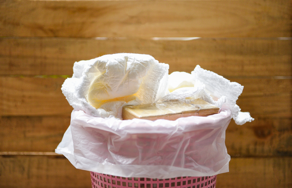 a pink baskey piled high with dirty diapers ona wood background
