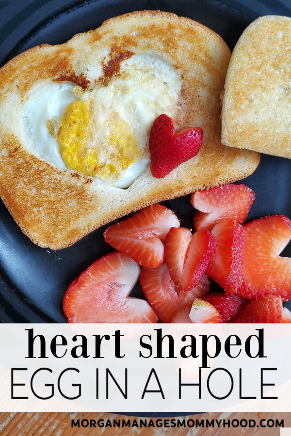 pinable image of a heart in a hole with aheart strawberries on a black plate with text overlay reading heart shaped egg in a hole