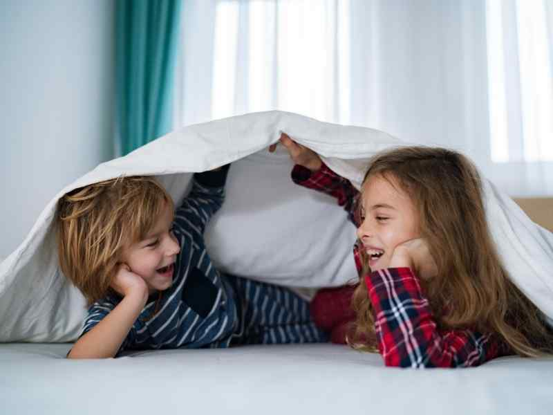a boy and a girl child giggling unfer white sheets wearing pajamas