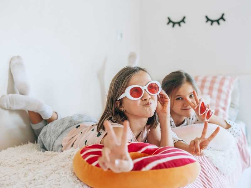 2 girls laying on a bed in pajamas wearing fun glasses and making faces