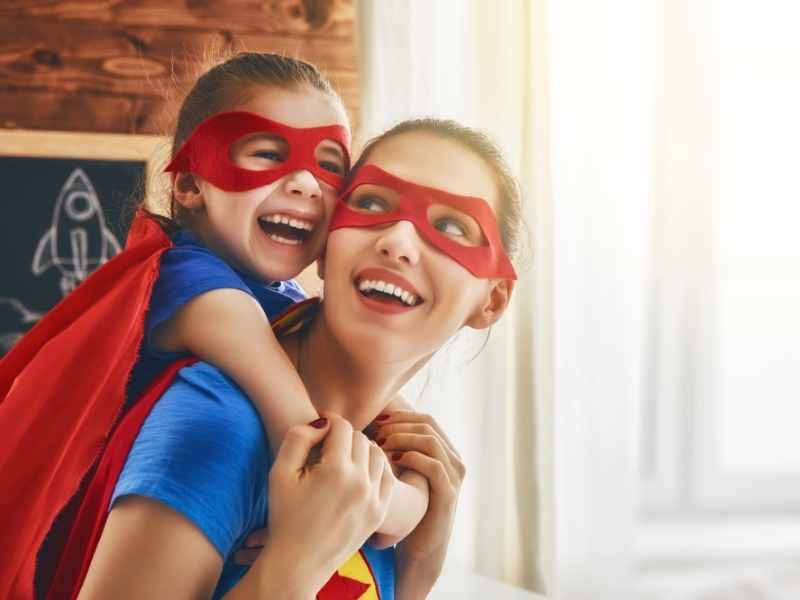 a mom and daughter wearing superhero costumes with the girl on the moms back
