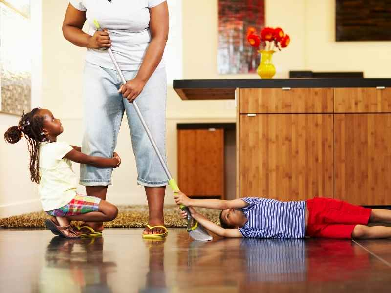 a mom has mopping with two kids clinging to her