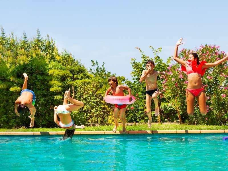 photo of five kids jumping into an inground pool with grass and bushes behind them